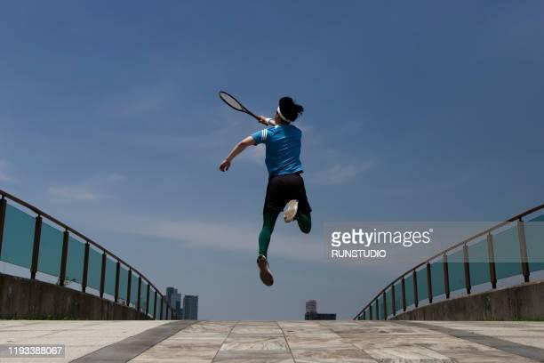 young man swinging tennis racket - スポーツ  ストックフォトと画像