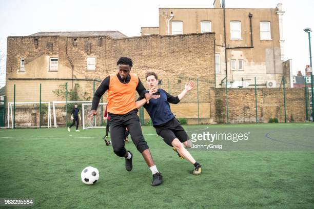 Young man tackling opponent on outdoor football pitch