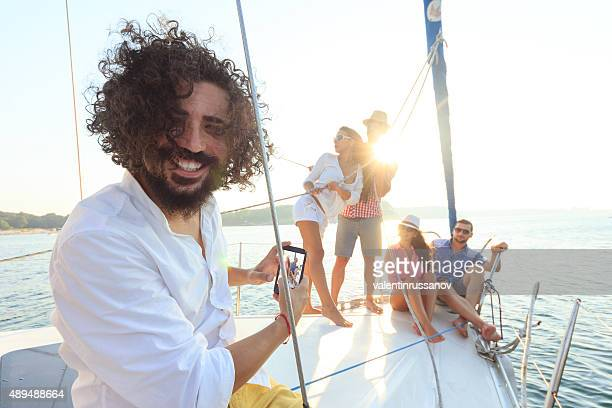 Young man take a pictures with smartphone on sailboat