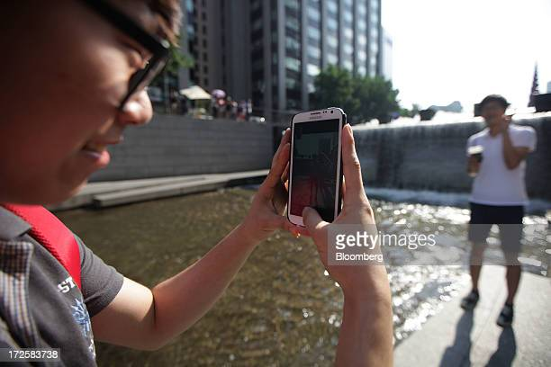 A young man takes a photograph with a Samsung Electronics Co smartphone at Cheonggye Stream in Seoul South Korea on Wednesday July 3 2013 Samsung...