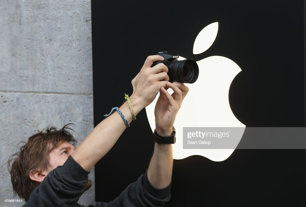 A young man takes a picture outside the Apple Store as people enter on the first day of sales of the new Apple iPhone 6 in Germany on September 19, 2014 in Berlin, Germany. Hundreds of people had waited in a line that went around the block through the night in order to be among the first people to buy the new smartphone, which comes in two versions: the Apple iPhone 6 and the somewhat larger Apple iPhone 6 Plus.