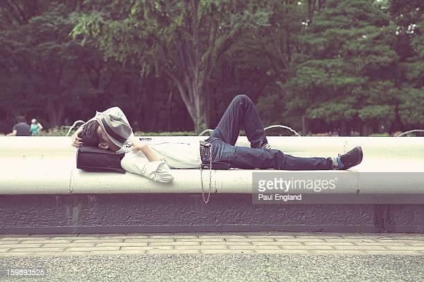 Young man takes at nap in Tokyo's Yoyogi Park