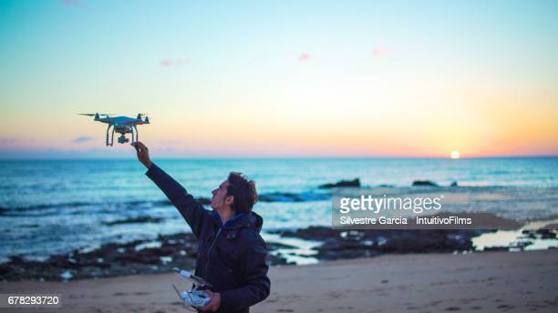 a young man takes his white quadcopter drone while it is flying at sunset in the beach - helicopter photos stock pictures, royalty-free photos & images