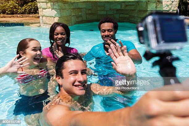 Young man takes photo with wearable camera in swimming pool