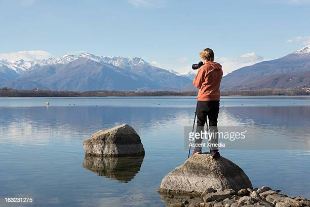 Young man takes picture from rock beside lakeshore