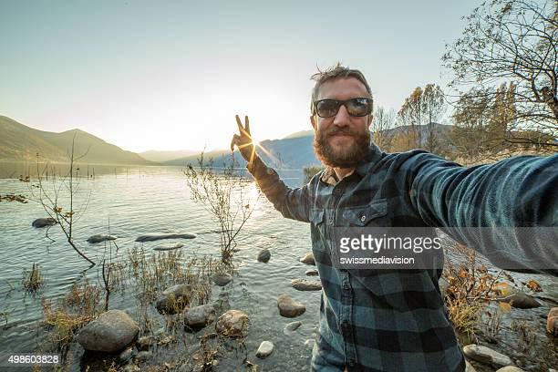 junger mann macht selfie-porträt in der natur mit handy - fotohandy stock-fotos und bilder