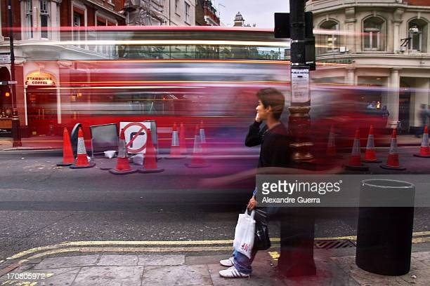 Young man taking a break and speaking on the phone, standing on the street whit a bus in motion in the background.