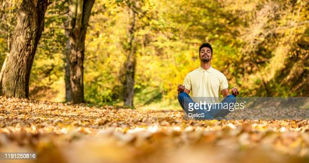 young man taking a break in nature and meditating. - mental wellbeing stock pictures, royalty-free photos & images