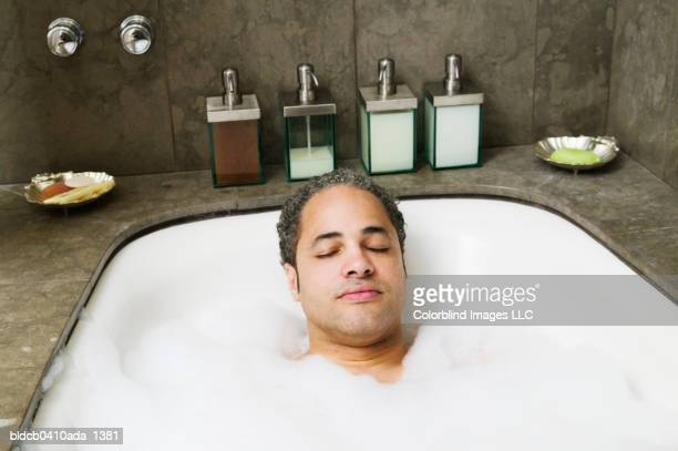 young man taking a bubble bath - bubble bath stock pictures, royalty-free photos & images
