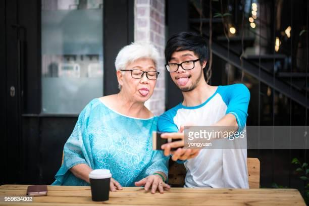 jeune homme tenant un selfie drôle avec sa grand-mère - mamie humour photos et images de collection