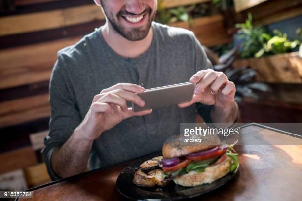 Jonge man die een foto van zijn vegetarische maaltijd heel gelukkig en lachende