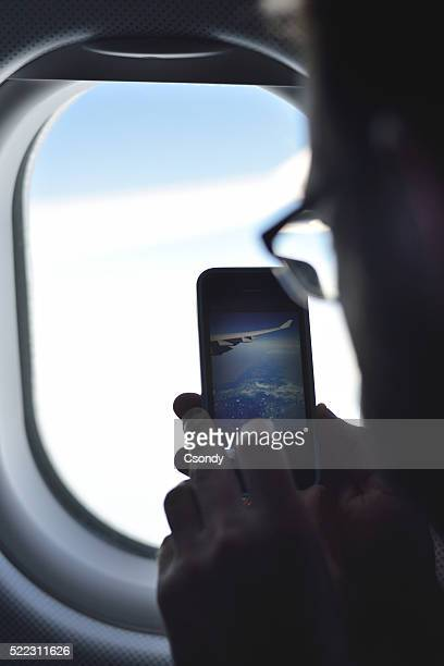 Young man taking a picture on an airplane