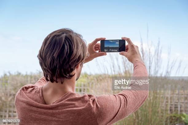 Young man taking a picture with camera phone