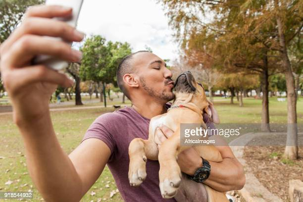 Young man taking a selfie of him kissing his puppy.