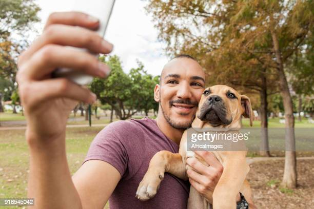 Young man taking a selfie of himself holding his puppy.