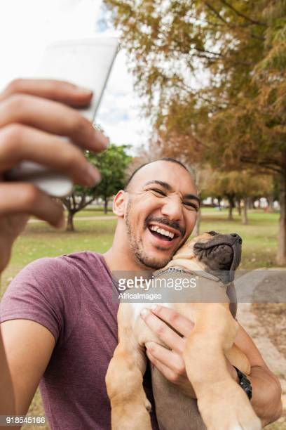 Young man taking a selfie of himself laughing with his puppy.