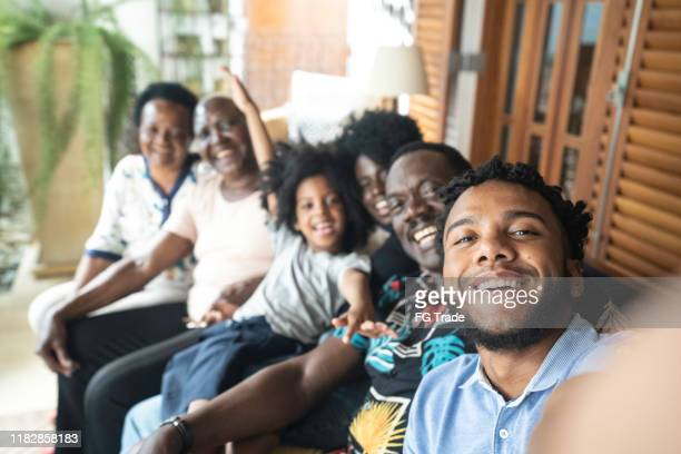 young man taking a selfie of his family - large family stock pictures, royalty-free photos & images