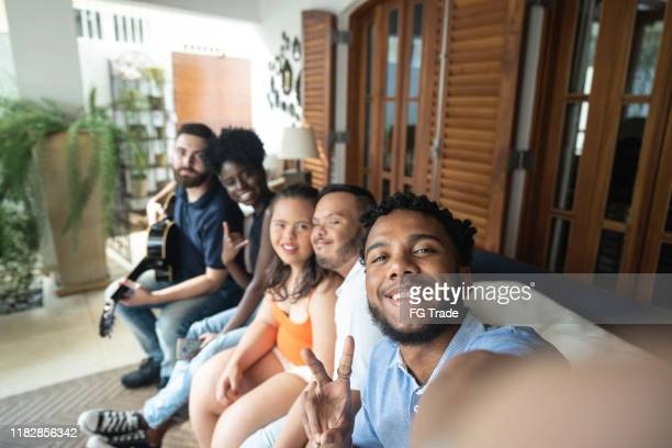 young man taking a selfie of his friends - intellectually disabled stock pictures, royalty-free photos & images