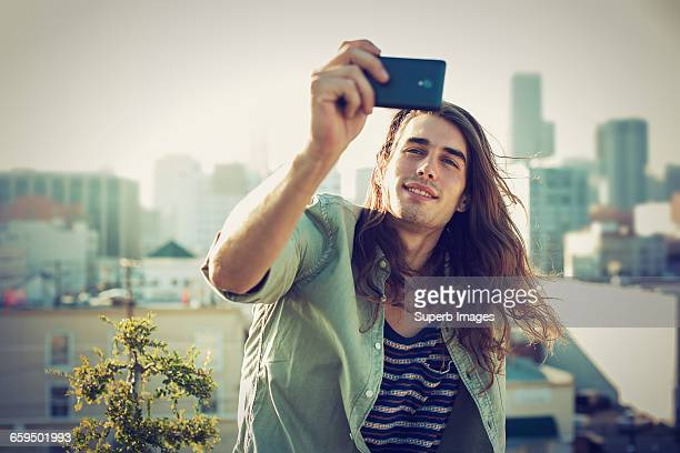 Young man taking a selfie on urban rooftop