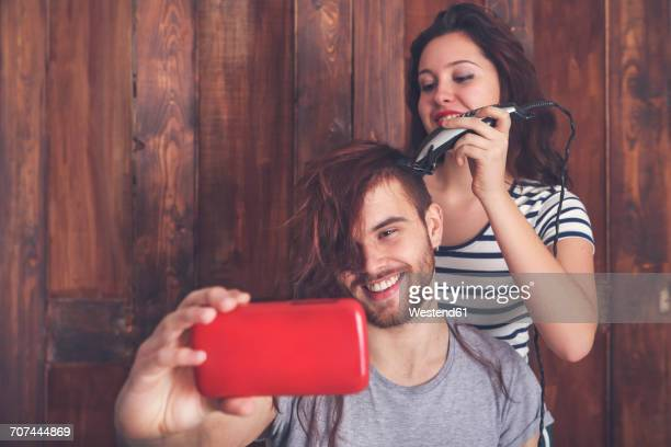 Young man taking a selfie while getting a haircut by his girlfriend with hair cutting machine