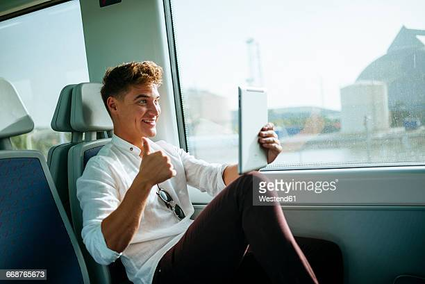 Young man taking a selfie with a tablet on a train