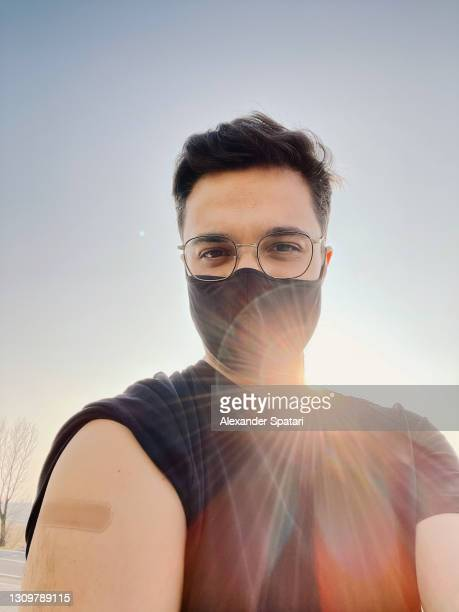 young man taking a selfie with band-aid on shoulder after getting vaccine for covid-19 - sunbeam stock pictures, royalty-free photos & images