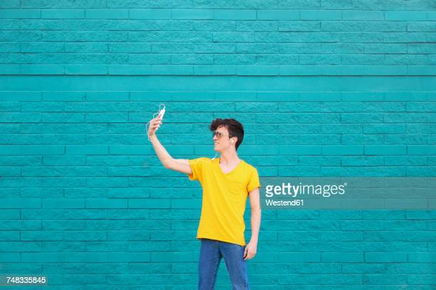Young man taking a selfie with smartphone in front of blue brick wall