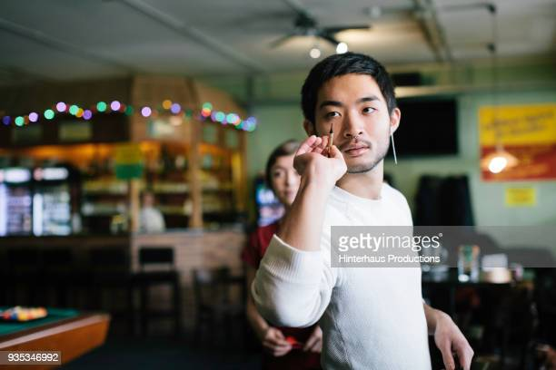 Young Man Taking A Shot Playing Darts