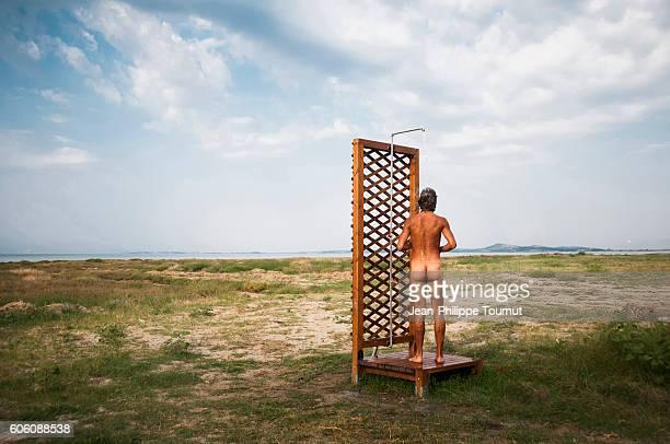 young man taking a shower outside in nature, greece - ragazzi fighi nudi foto e immagini stock
