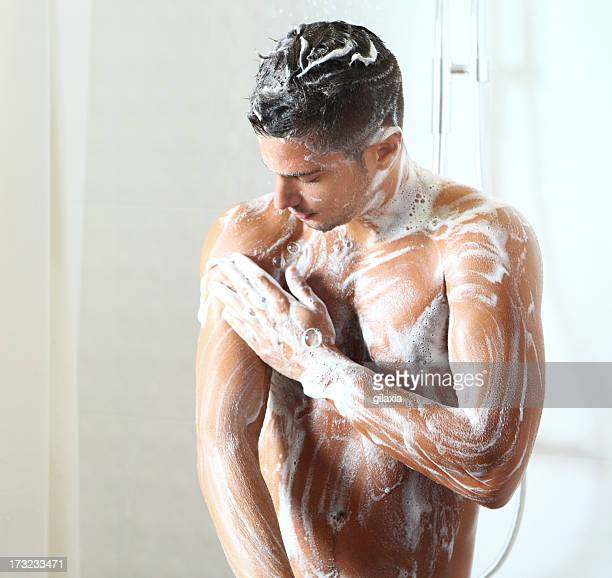 Young man taking a shower.