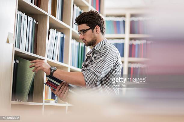 Young man taking books in a library.