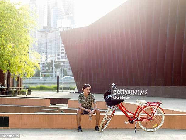 Young man taking break beside bicycle, Southbank, Melbourne, Australia