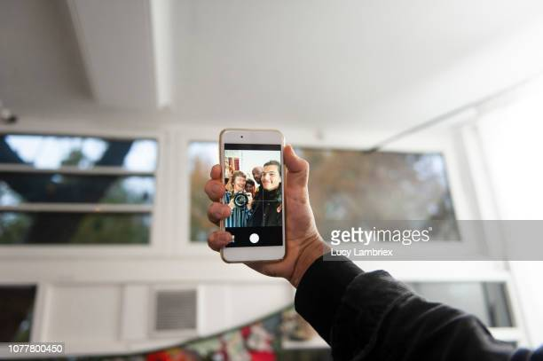 Young man taking group selfies at a creative pop up store