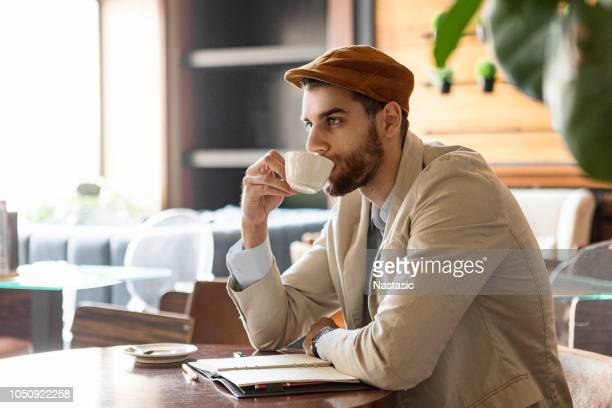 young man taking notes in cafe - poet stock pictures, royalty-free photos & images