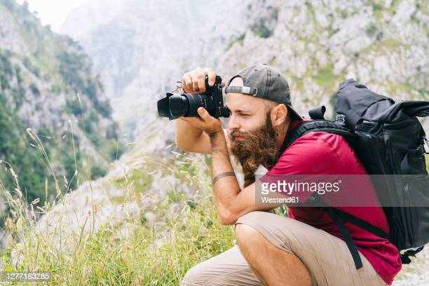young man taking photo through camera while sitting on mountain at ruta del cares, asturias, spain - photographer stock pictures, royalty-free photos & images