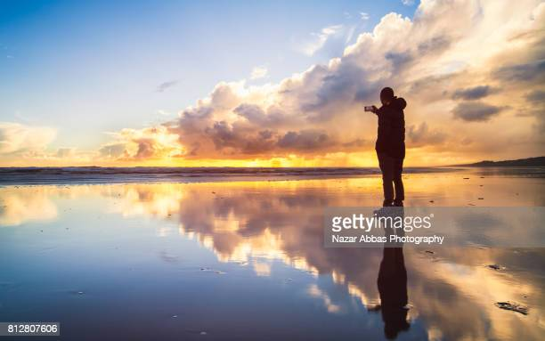 Young Man Taking Photo With His Smart Phone At Beach.