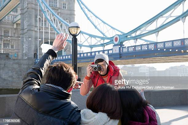 Young man taking photograph of friends at Tower Bridge, London, England