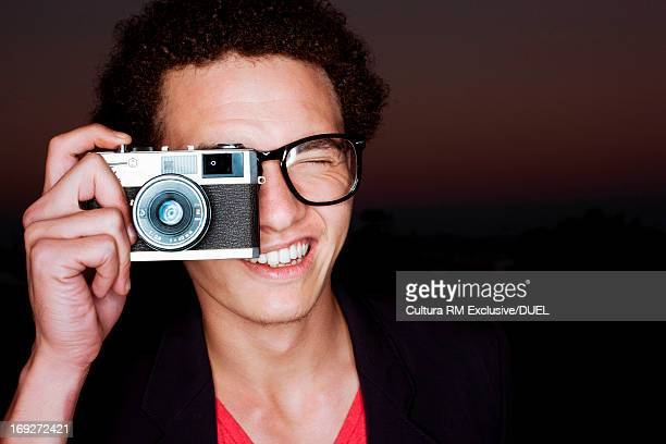 Young man taking photograph with camera