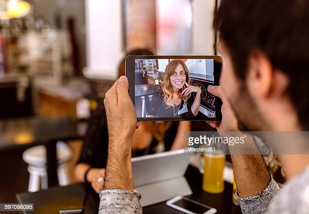 Young man taking photography of his girlfriend with digital tablet