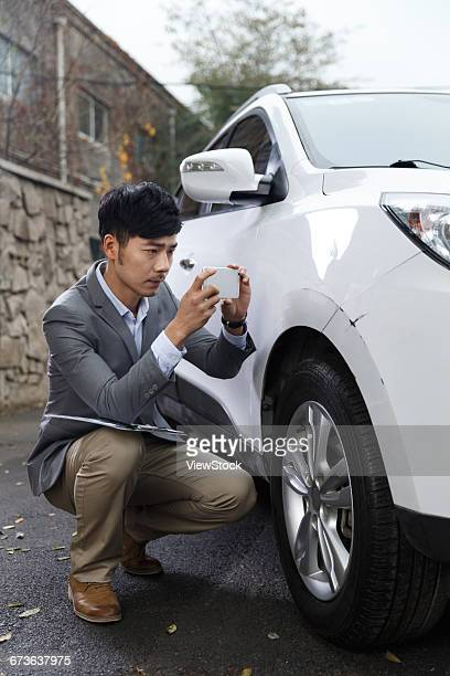 Young man taking photos of car scratch