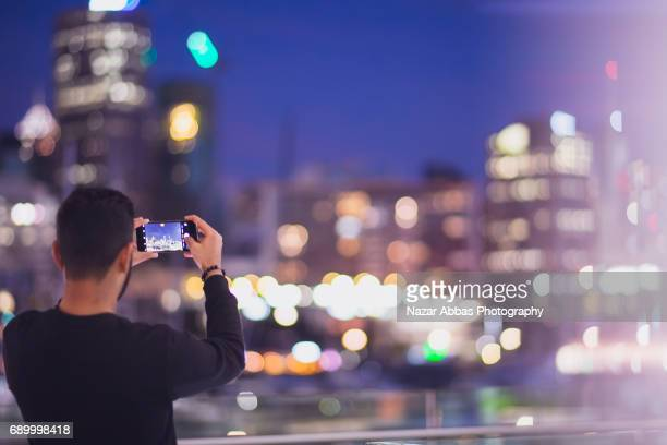 Young Man Taking Photos Of City With His Smart Phone.