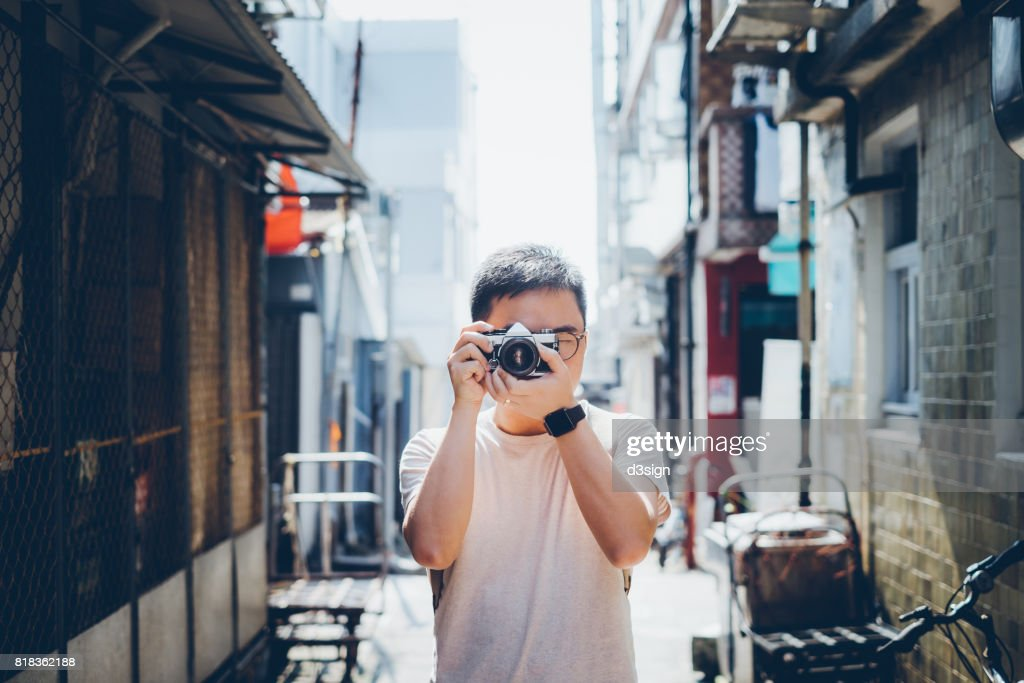 Young man taking photos with retro film camera in city street : Stock Photo