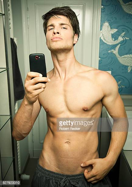young man taking picture of himself by mobile in mirror - eitelkeit stock-fotos und bilder