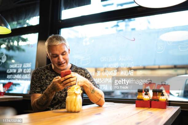 young man taking picture of his milkshake - cardiff wales stock pictures, royalty-free photos & images