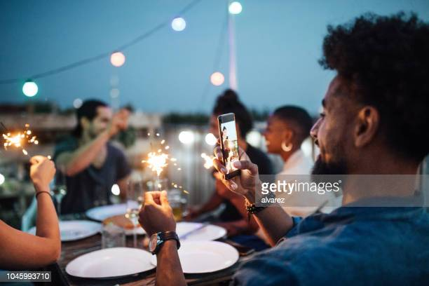 young man taking picture of sparkler at rooftop party - photographing stock pictures, royalty-free photos & images