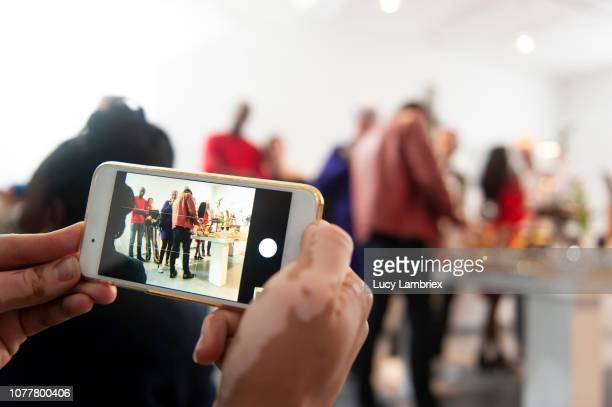 young man taking pictures at a creative pop up store - pop up store stock pictures, royalty-free photos & images