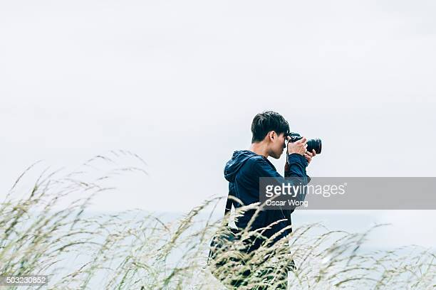 Young man taking pictures by the sea