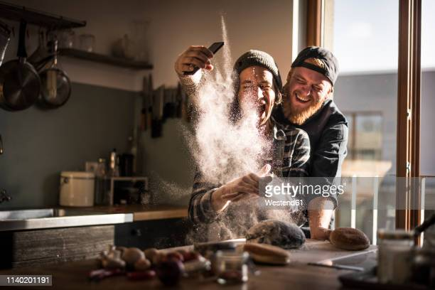 young man taking pictures of his friend, cooking in the kitchen - spaß stock-fotos und bilder