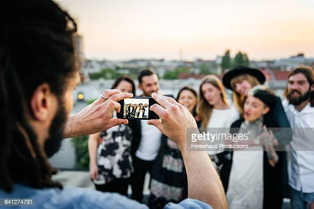 young man taking pictures of his friends - 写真を撮る ストックフォトと画像