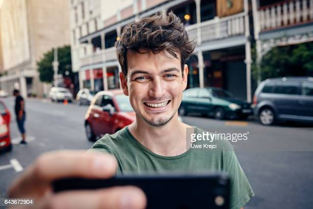 Young man taking self portrait in the city
